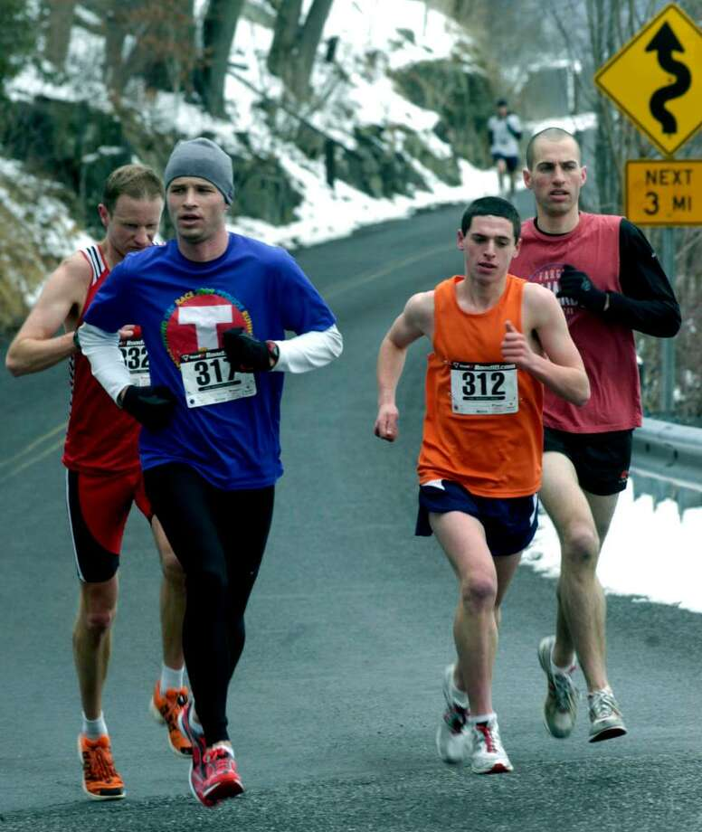 SPECTRUM/Leading the field of 377 Polar Bear Run finishers near the three-mile mark close to the Washington town beach are eventual champion Tim Perry (317), Asher Brandt (312), former champ Joe Lemay (332) and an unidentified runner.  Feb. 28, 2010. Photo: Norm Cummings / The News-Times