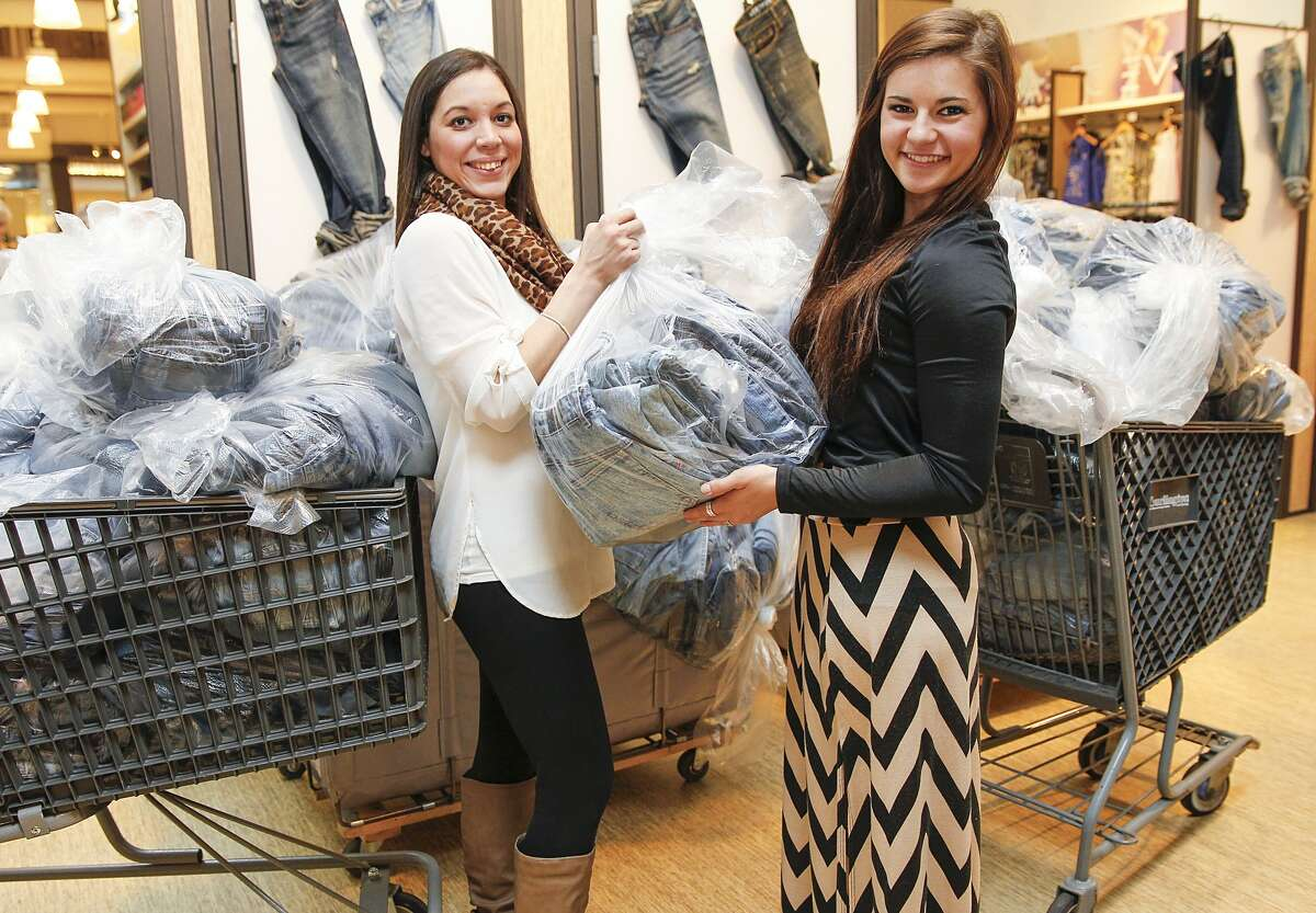 Peyton Green, a senior at Foster High School, hands a bag of jeans to Aeropostale store manager Monica Padro, as part of the 800 pairs of jeans she is donating through DoSomething.org and Aeropostale located at Katy Mills Mall. Green will receive one entry for a $10,000 college scholarship for every two pairs of jeans she donates, resulting in 400 entries.