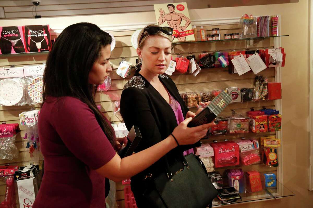Friends Brittany Garrido (left) and Kaili Linville look over a starter bondage kit in the Good Vibrations store on Mission Street in S.F.