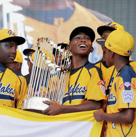 Players from the Jackie Robinson West Little League in Chicago enjoy their national championship in August. The title has been stripped because some players came from outside league boundaries.