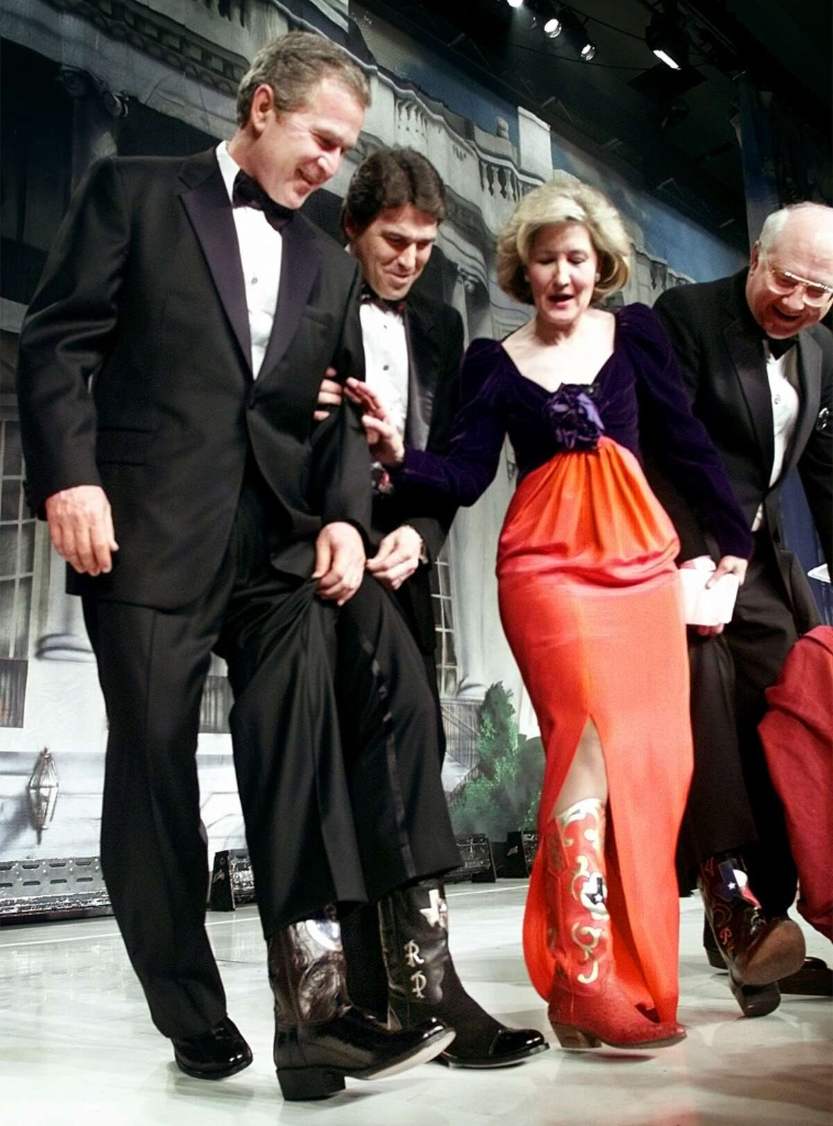 Then President-elect Bush compares boots with Rick Perry, Sen. Kay Bailey Hutchison and Sen. Phil Gramm on stage during the Black Tie and Boots ball in Washington Friday night, Jan. 19, 2001.