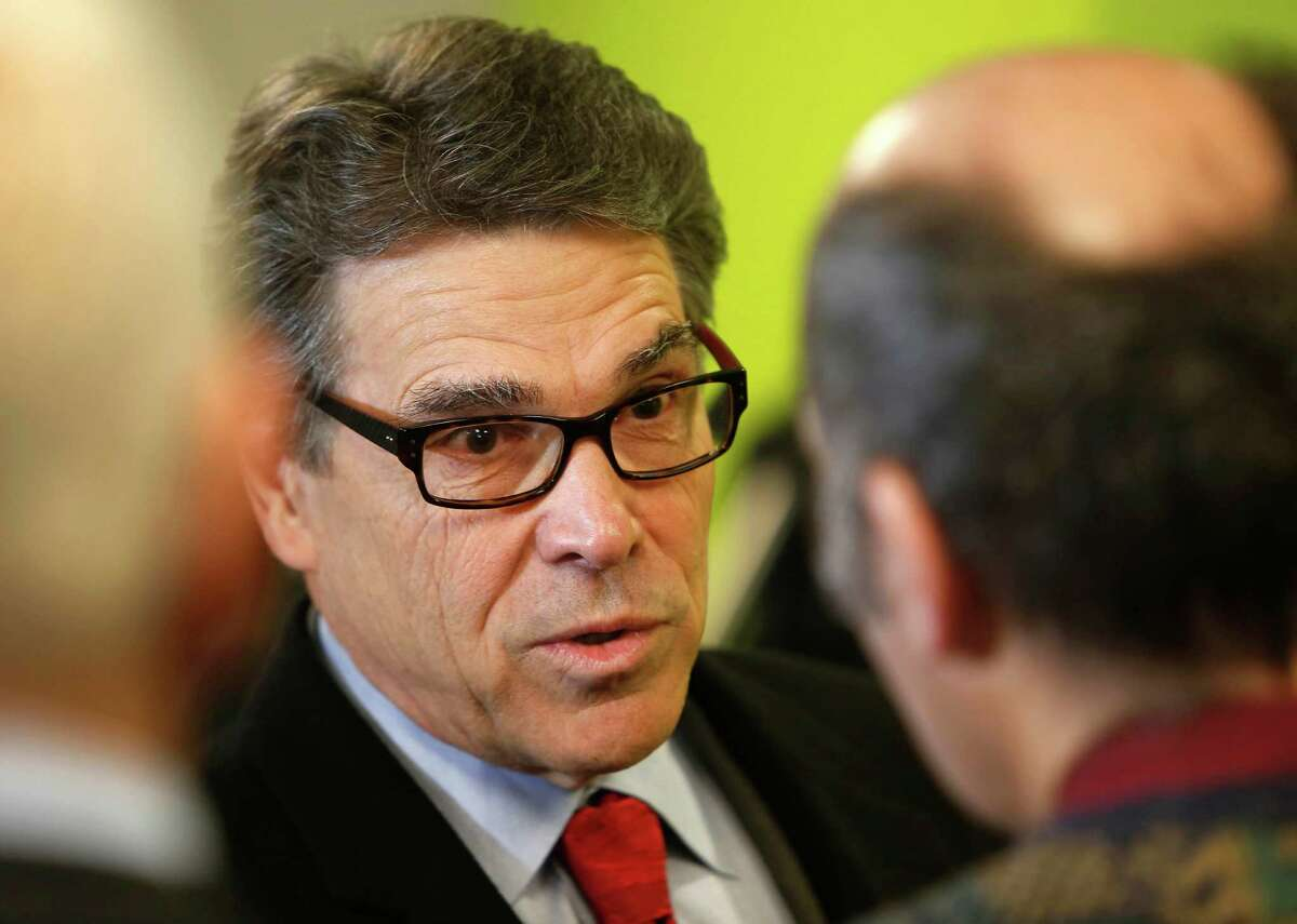 """Former Texas Gov. Rick Perry talks to Paul Blackford before meeting with area business leaders, Wednesday Feb. 11, 2015, in Bedford, N.H. The former 2012 presidential hopeful told them he's """"just warming up"""" when he arrived in freezing cold New Hampshire and said he's carefully preparing for a possible presidential campaign."""