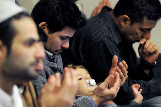 Hassan Elminyaw, center, and his two-year-old son Samy attend the midday prayer and memorial service Friday, Feb. 13, 2015, at the Masjid As-Salam Mosque in Albany, N.Y., for Ashiqur Rahman, the 4-year-old boy hit by a garbage truck Thursday on Central Avenue. (Michael P. Farrell/Times Union) Photo: Michael P. Farrell / 00030605A