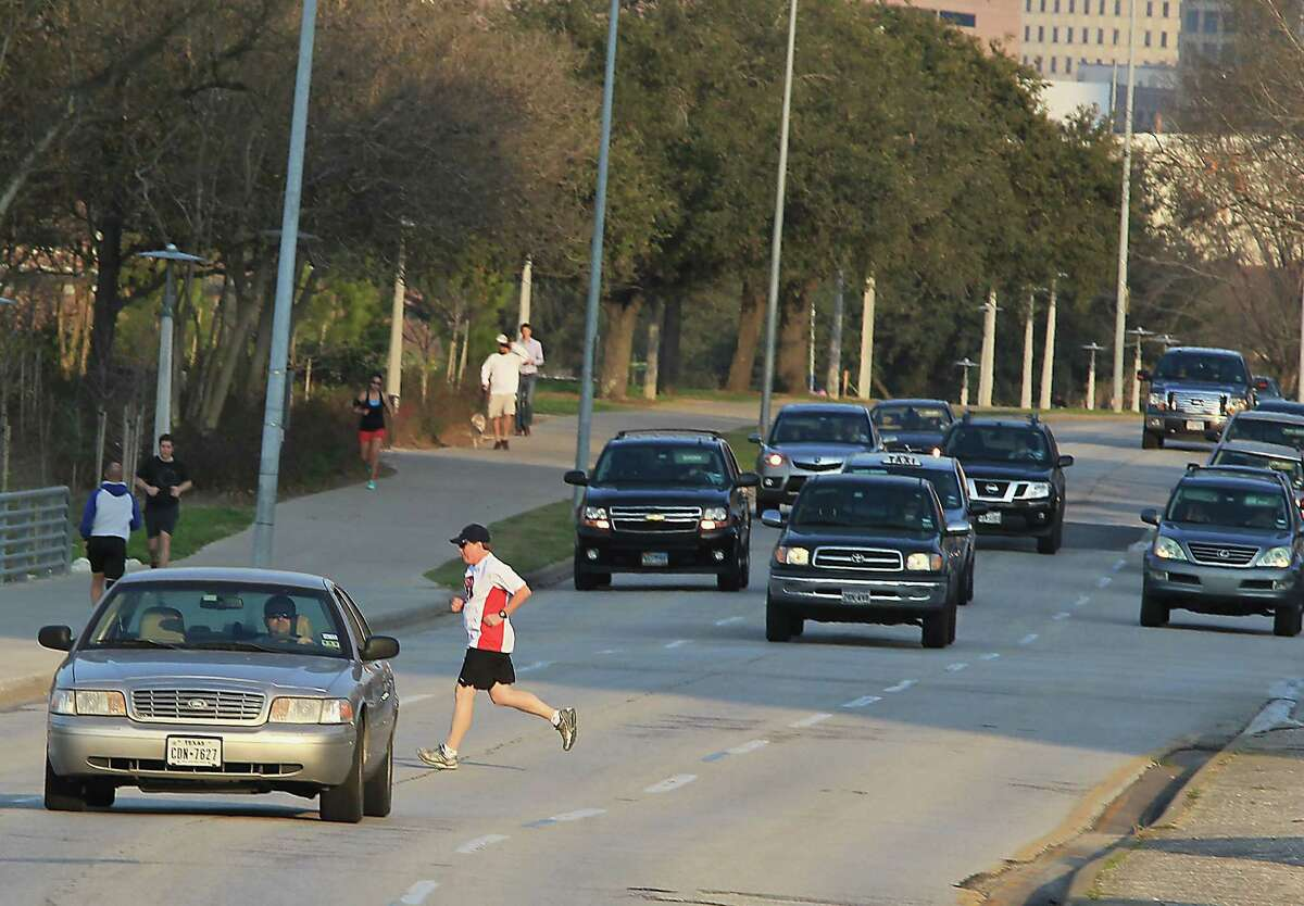 Pat Dunnahoo center, jogs across Allen Parkway near Taft Street on Feb. 12. Houston officials are planning a $10 million rehab of Allen Parkway that turns it back into what it was originally intended to be by making it less of a freeway and more of a parkway with trees and pedestrian crossings.