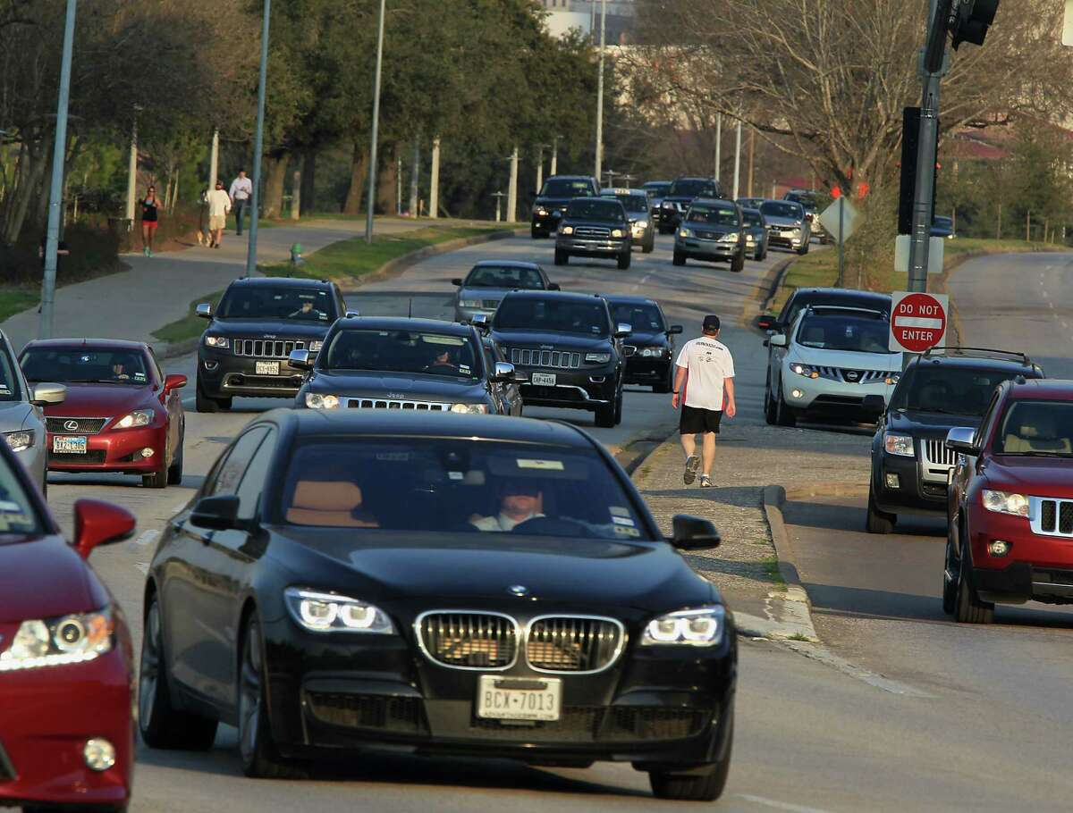 Pat Dunnahoo center, waits for traffic to cross Allen Parkway near Taft street on Feb. 12. How traffic and pedestrian access is handled is part of a new transportation discussion in Houston.