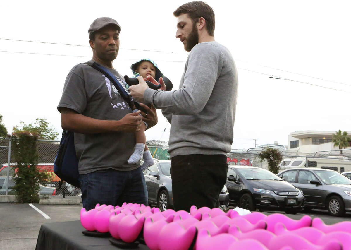 Lyft driver Christopher Carbins (left) receives the company's new logo mustache for his car.