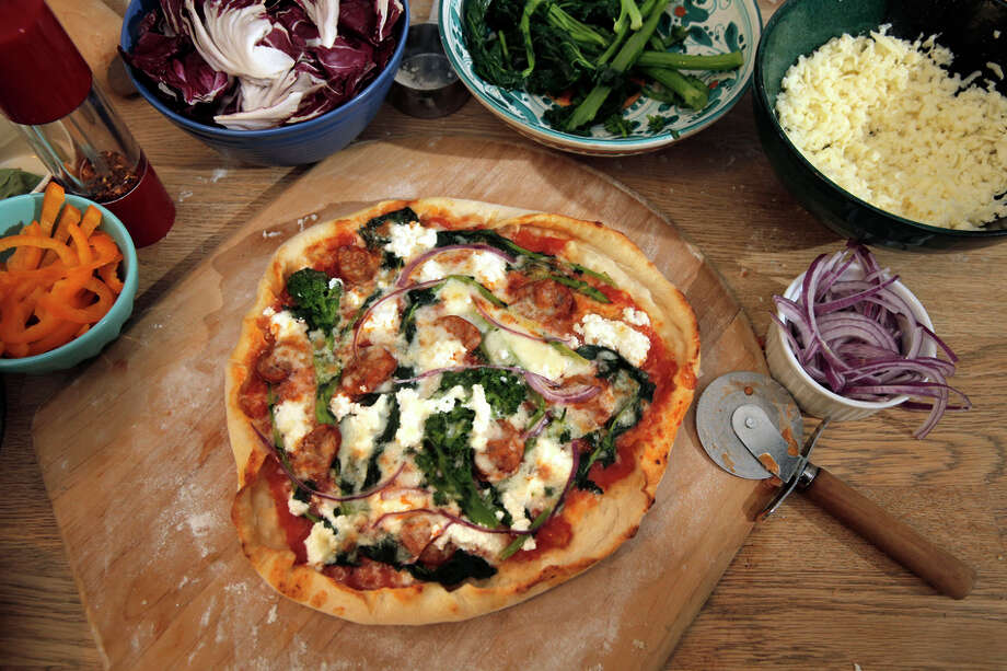 Fresh out of the oven, a pizza with blanched broccoli rabe, slivered onions, a mix of cheeses and spicy sausage. Photo: Carlos Avila Gonzalez / The Chronicle / ONLINE_YES