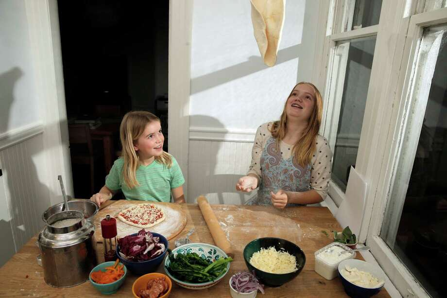 It's a toss-up: Nine-year-old Elsie (left) and Dahlia Gustafson, 12, make pizza from scratch under the tutelage of their mom, Chronicle writer Tara Duggan. Dahlia's dough goes airborne before being tricked out with toppings. Photo: Carlos Avila Gonzalez / The Chronicle / ONLINE_YES