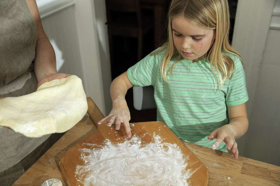 Elsie Gustafson, 9, adds flour to a pizza peel as she bakes with her mom, Chronicle writer Tara Duggan, at their home in San Francisco. Photo: Carlos Avila Gonzalez / The Chronicle / ONLINE_YES
