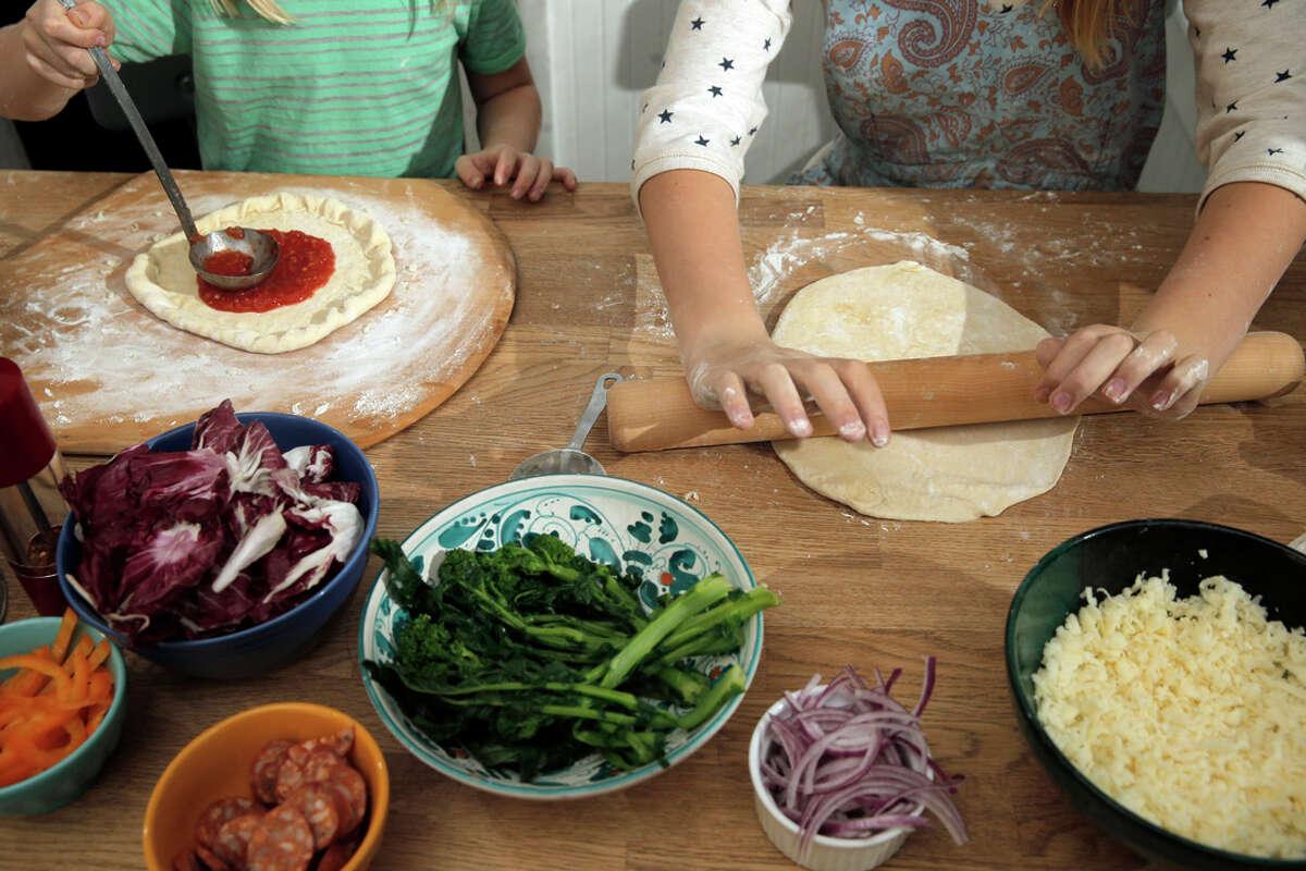 Elsie (left) and Dahlia Gustafson craft homemade pizzas with their mom, Chronicle writer Tara Duggan, at their home in San Francisco.