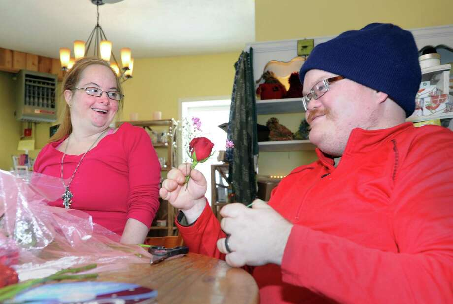 Kristy Kasmarski, left, smiles after giving the boutonniere she made to her boyfriend, Chris Walker, at Abilis in Greenwich, Conn., Friday, Feb. 13, 2015. Kasmarski and Walker are both clients of Abilis and are taking part in the Sweethearst Dance that is being held at the Athur Murray Grande Ballroom in Greenwich on Saturday night (Valentine's Day evening), where the boutonnieres will be exchanged for corsages by the Abilis couples. According to Doreen Harrison, an Abilis job coach who was leading the boutonniere making, 10 couples will be exchanging flowers with each other and dancing the night away courtesy of the Arthur Murray Dance Studio of Greenwich. Abilis is a greenwich organization that serves people with developmental disabilities. Photo: Bob Luckey / Greenwich Time