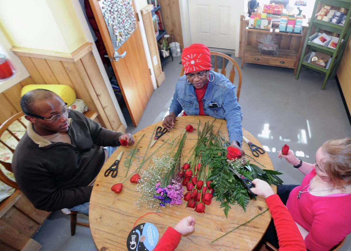 At center, Doreen Harrison, an Abilis job coach, leads a group of Abilis clients, including Theo Brown, left, and Kristy Kasmarski, right, in the fine art of boutonniere making at Abilis in Greenwich, Conn., Friday, Feb. 13, 2015. The boutonnieres will be exchanged for corsages by Abilis couples during the Sweethearst Dance that is being held at the Arthur Murray Grande Ballroom in Greenwich on Saturday night (Valentine's Day evening). According to Harrison, 10 couples will be exchanging flowers with each other and dancing the night away courtesy of Arthur Murray Dance Studio of Greenwich. Abilis is a greenwich organization that serves people with developmental disabilities.
