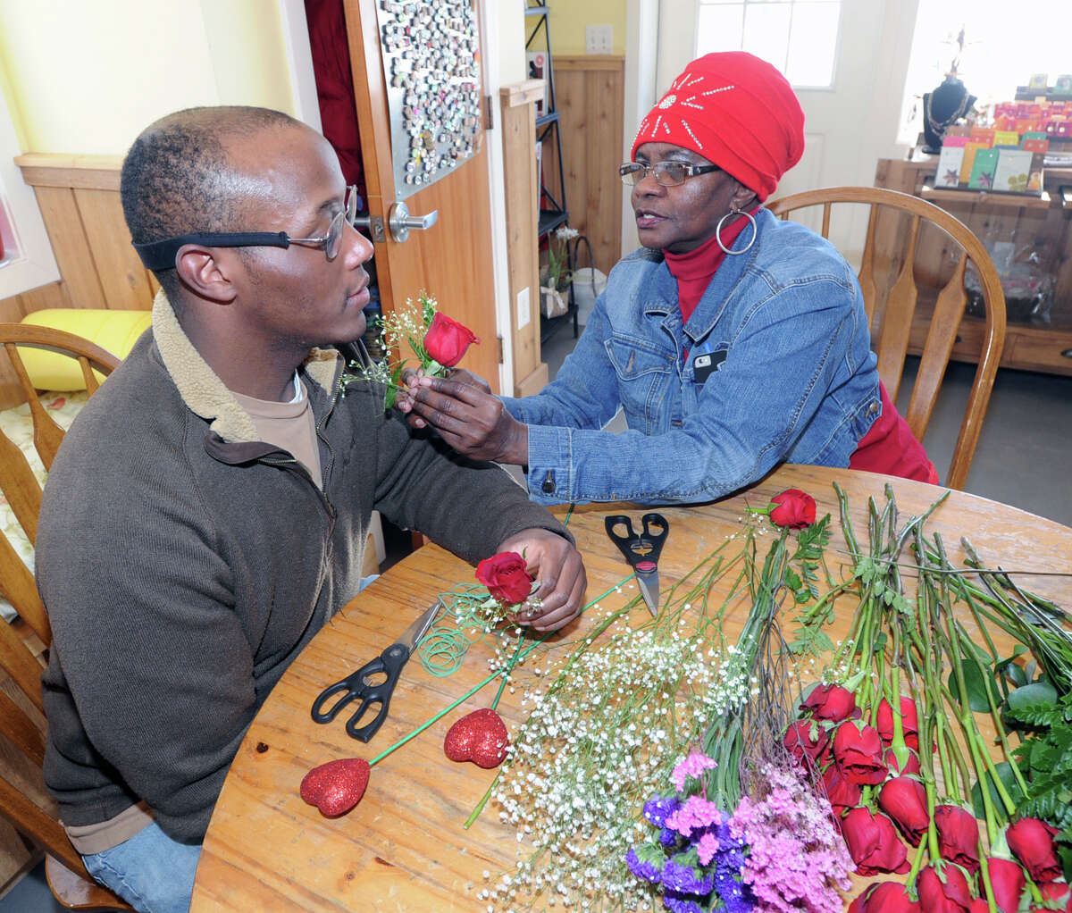 Abilis client Theo Brown, left, gets a lesson in boutonniere pinning from Doreen Harrison (red hat), an Abilis job coach, who was leading a group of Abilis clients in the fine art of boutonniere making at Abilis in Greenwich, Conn., Friday, Feb. 13, 2015. The boutonnieres will be exchanged for corsages by Abilis couples during the Sweethearst Dance that is being held at the Arthur Murray Grande Ballroom in Greenwich on Saturday night (Valentine's Day evening). According to Harrison, 10 couples will be exchanging flowers with each other and dancing the night away courtesy of Arthur Murray Dance Studio of Greenwich. Theo Brown said he will be attending the dance with his girlfriend, Wendy. Abilis is a greenwich organization that serves people with developmental disabilities.