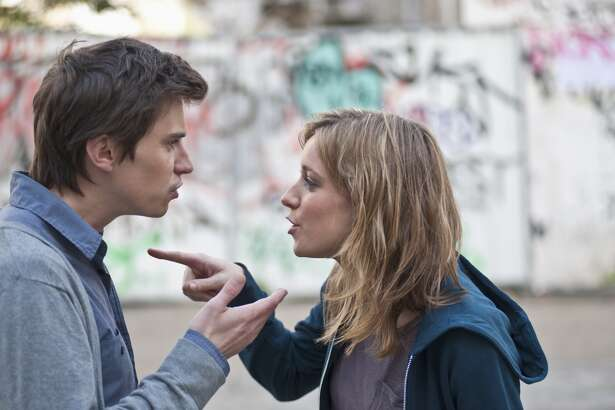 Young couple arguing in street fighting breakup