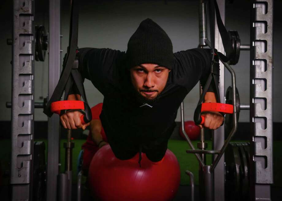 Fitness expert and owner of Nine Innovations gym Abdul Foster performs a stability push up, using straps and a stability ball Thursday January 22, 2015 at Nine Innovations gym in Houston,Texas. (Billy Smith II / Houston Chronicle) Photo: Billy Smith II, Staff / © 2015 Houston Chronicle