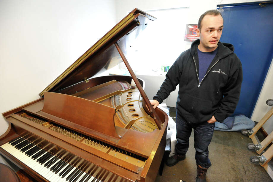 Yury Feygin, owner of Amadeus Piano, shows off a Steinway piano on display at his business in Stamford, Conn., on Wednesday, Feb. 4, 2015. The piano company mainly deals with tuning, repairs, moving, storage, restoration and antique piano sales with locations in Westport and Long Island, NY. Photo: Jason Rearick / Stamford Advocate