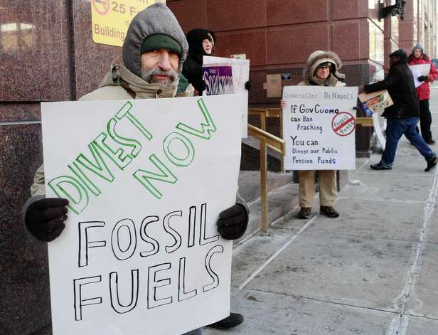 Joe Seeman, left, of Ballston Spa holds a sign during a rally to urge NYS to divest all pension funds from fossil fuels outside the the NYS Comptrollers office Friday Feb. 13, 2015, in Albany, NY.   (John Carl D'Annibale / Times Union) Photo: John Carl D'Annibale / 00030573A