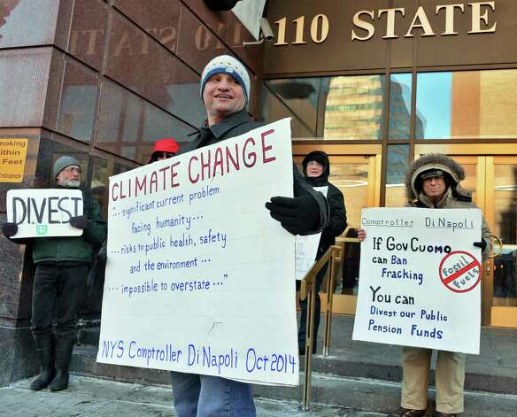 David Gardiner, center, of Albany holds a sign during a rally to urge NYS to divest all pension funds from fossil fuels outside the the NYS Comptrollers office Friday Feb. 13, 2015, in Albany, NY. (John Carl D'Annibale / Times Union)
