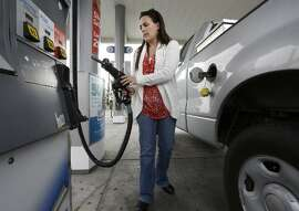 FILE - In this Nov. 12, 2014 file photo, Lydia Holland replaces the gas nozzle after filling up at a gas station in Sacramento, Calif. The Energy Department on Tuesday, Dec. 9, 2014 again slashed its prediction for next year's average price of gasoline across the U.S., this time to $2.60 a gallon. That's 23 percent below the projected average for this year and the lowest since 2009.