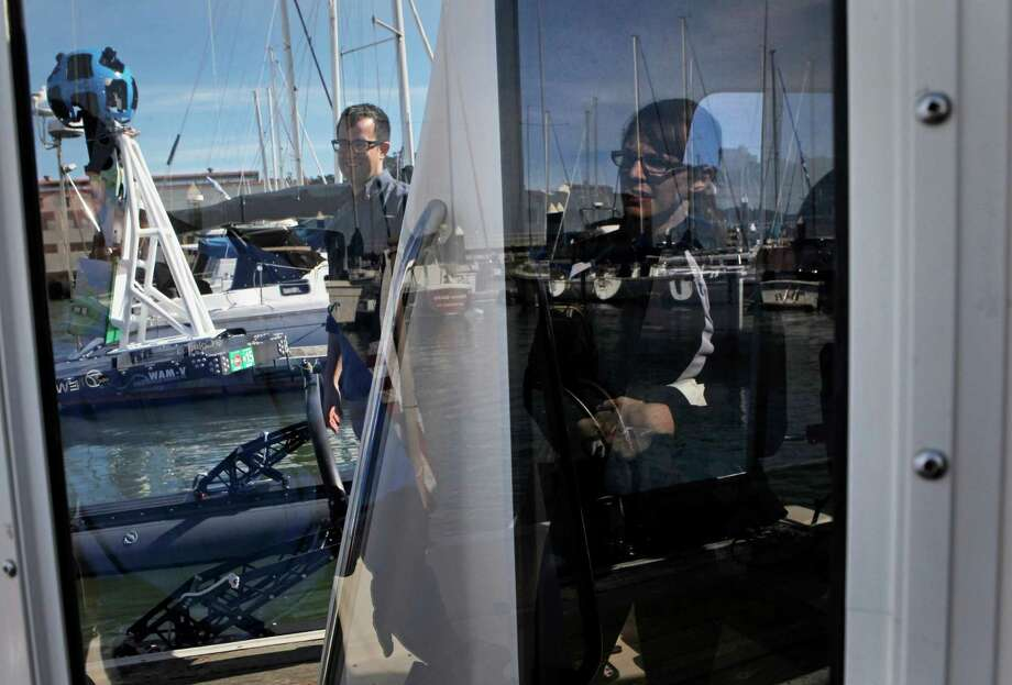 In the San Francisco marina, Ian Wren, a Baykeeper scientist, along with Karin Tuxen Bettman of Google explain technologies relating to rising tide levels. Photo: Sophia Germer / The Chronicle / ONLINE_YES
