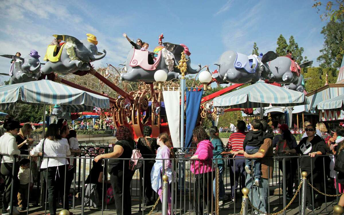 FILE - In this Jan. 22, 2015, file photo, visitors wait in line to board the Dumbo the Flying Elephant ride at Disneyland in Anaheim, Calif. State health officials declared California's measles outbreak, which they said began in Disneyland and a neighboring Disney theme park, officially over Friday. (AP Photo/Jae C. Hong, File)