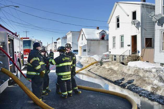 Albany firefighters on the scene of a fire at 449 Second Street, right, Friday Feb. 13, 2015, in Albany, NY.  (John Carl D'Annibale / Times Union) Photo: John Carl D'Annibale