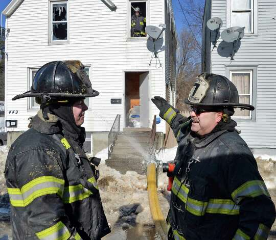 Firefighter Brendan Rhatigan, left, and Lt. Fred Peters in front of fire scene at 449 Second Street, right, Friday Feb. 13, 2015, in Albany, NY.  (John Carl D'Annibale / Times Union) Photo: John Carl D'Annibale