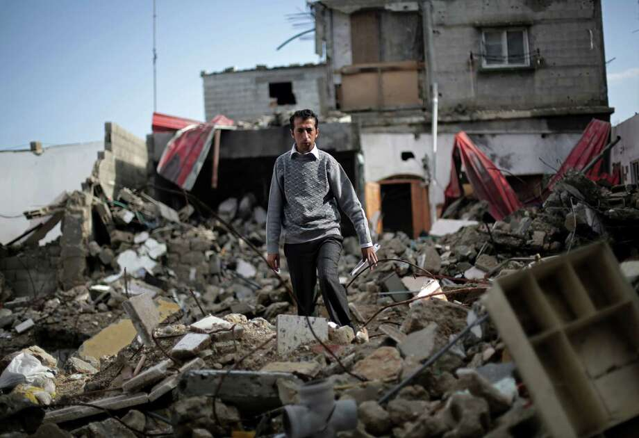 Mahmoud Abu Amer, 37, walks amid the ruins of an apartment building where 16 relatives were killed by an Israeli airstrike on July 29 in Khan Younis, Gaza. The building was one of scores targeted by Israel in its war with Hamas. At least 844 Palestinians, the youngest 4 days old and oldest 92, died when their homes were hit. Photo: Adel Hana, STF / AP