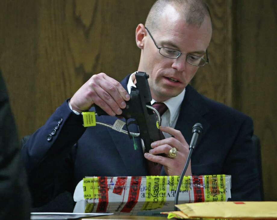 Department of Public Safety forensic scientist James Jeffress examines one of two pistols that matched bullet fragments taken from the bodies of Chris Kyle and Chad Littlefield. Jeffress was a witness for the prosecution Friday in the murder trial of Eddie Ray Routh in Stephenville. Photo: Paul Moseley, MBR / Fort Worth Star-Telegram