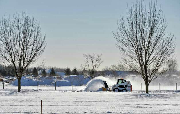 Parks and Rec employee Peter Austin uses a Bobcat to clear snow from walking paths at The Crossings of Colonie Friday Feb. 13, 2015, in Colonie, NY.  (John Carl D'Annibale / Times Union) Photo: John Carl D'Annibale / 00030608A