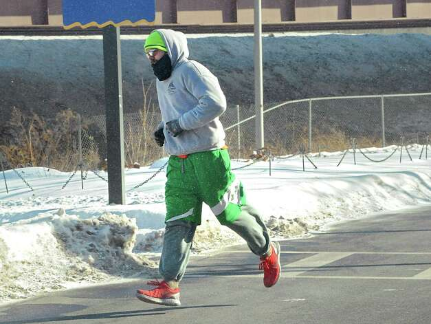 A bundled up jogger makes his way across Broadway during frigid weather Friday, Feb. 13, 2015 in Albany, N.Y. (Lori Van Buren / Times Union) Photo: Lori Van Buren / 00030608A