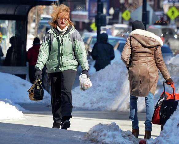 Terri Gile of Averill Park, left, braves wind and cold as she makes her way along Pearl Street Friday Feb. 13, 2015, in Albany, NY.  (John Carl D'Annibale / Times Union) Photo: John Carl D'Annibale / 00030608A