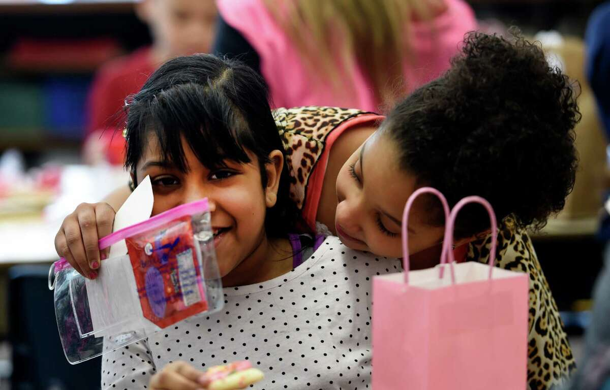 Amesha Bacchus, left, gets a big hug from Savinah Poole after Poole opened her Valentine's Day card Friday afternoon Feb. 13, 2015 at the Elmer Elementary School in Schenectady, N.Y. The occasion was Mrs. Jennifer Rodecker's class Valentine's Day celebration. (Skip Dickstein/Times Union)