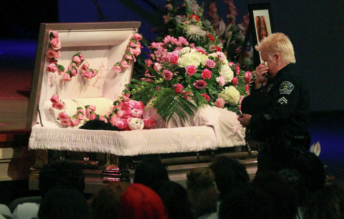 A police officer pays respects Friday February 13, 2015 at the casket of Samantha Elizabeth Dean during her funeral at Community Bible Church in San Antonio. Dean, who worked for the Kyle, Texas Police Department as the coordinator for its Victims Service Unit, was found dead on February 4 lying next to a car behind a building near Bastrop, Texas. Dean, who was pregnant, was shot in the head.