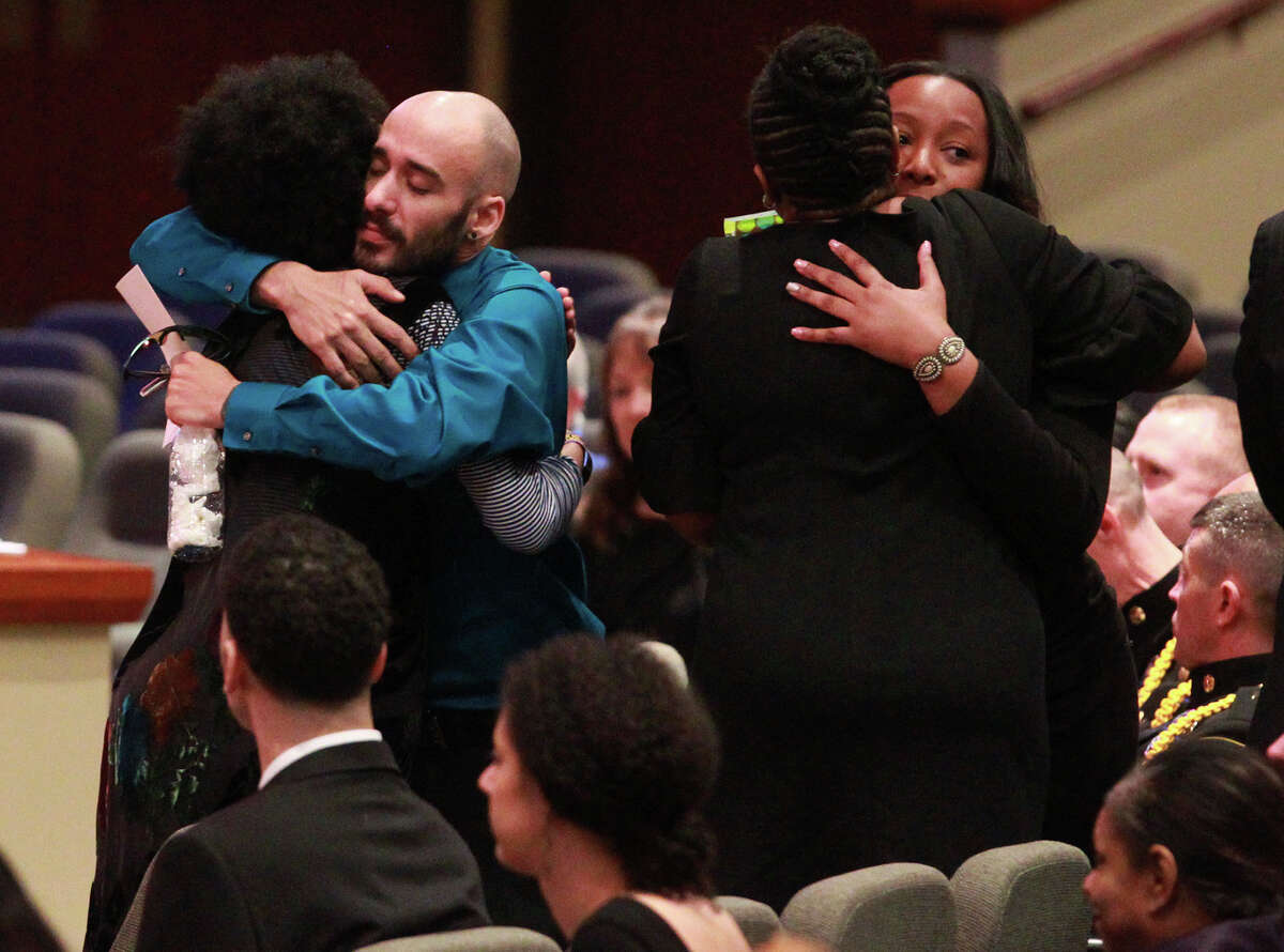 Mourners console each other Friday February 13, 2015 near the casket of Samantha Elizabeth Dean during her funeral at Community Bible Church in San Antonio. Dean, who worked for the Kyle, Texas Police Department as the coordinator for its Victims Service Unit, was found dead on February 4 lying next to a car behind a building near Bastrop, Texas. Dean, who was pregnant, was shot in the head.