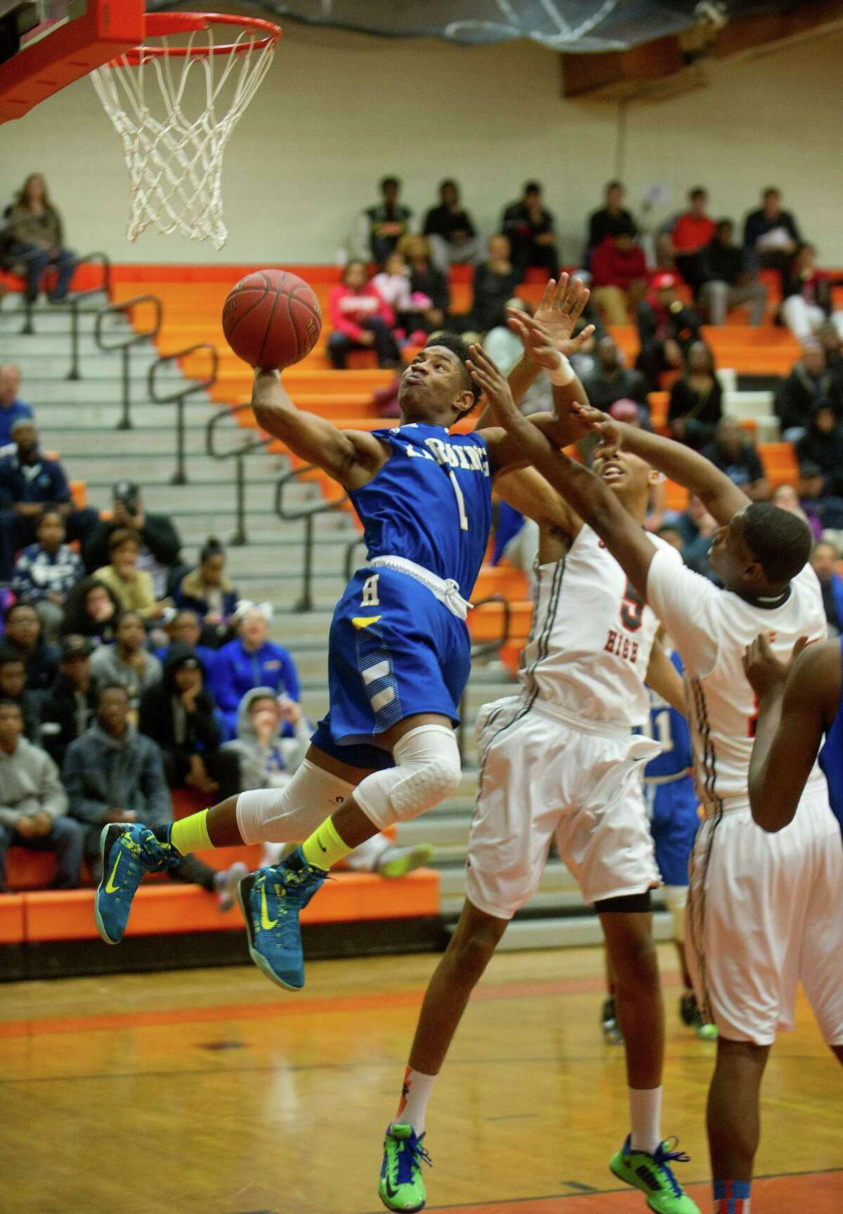 Harding's T.J. Killings jumps to take a shot during Friday's basketball game at Stamford High School on February 13, 2015. After the shot, Killings fell and injured his shoulder.