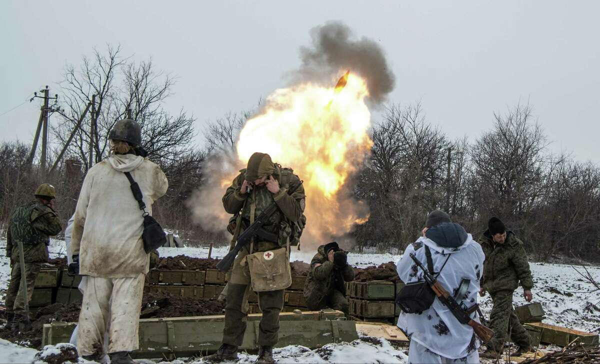 FILE - In this Wednesday, Feb. 11, 2015, file photo, Russian-backed separatists cover their ears as they fire a mortar towards Ukrainian troops outside the village of Sanzharivka, northeast of Debaltseve, eastern Ukraine. Ukraine says that eight troops have been killed and 34 wounded overnight, despite a peace deal and a looming cease-fire deadline. Vladislav Seleznyov, spokesman for the Ukrainian army general staff, said in comments carried by Interfax-Ukraine news agency on Friday that much of the fighting had taken place in Debaltseve, a key transport hub that has been hotly contested in recent days. (AP Photo/Maximilian Clarke, File) ORG XMIT: LON104
