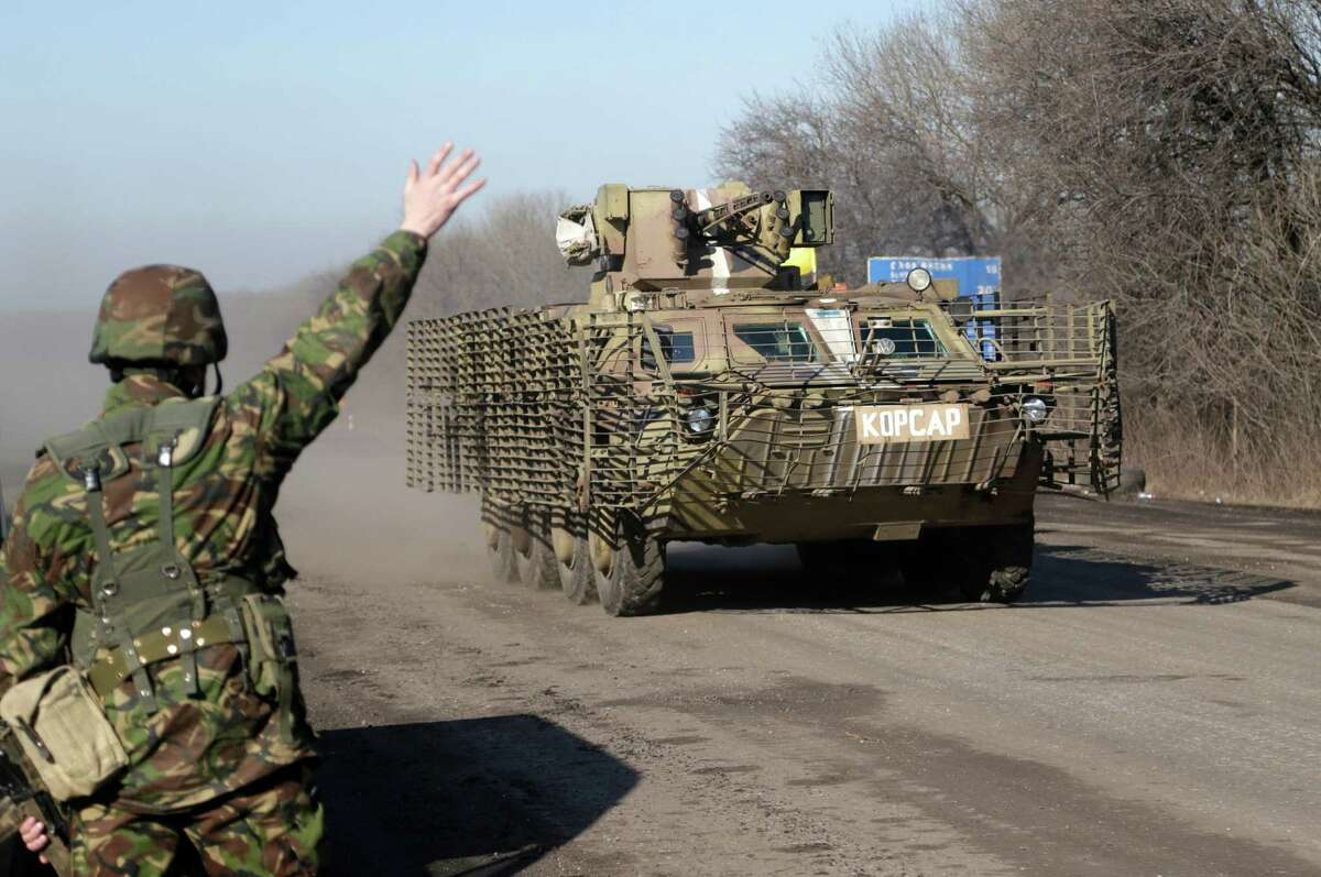 A Ukrainian government troop waves to a armored vehicle driving on the road towards Debaltseve near the town of Artemivsk, Ukraine, Friday, Feb. 13, 2015. The fighting between Russia-backed separatists and Ukrainian government forces has continued despite the agreement reached by leaders of Russia, Ukraine, Germany and France in the Belarusian capital of Minsk on Thursday. Much of the fighting had taken place near Debaltseve, a key transport hub that has been hotly contested in recent days. The leaders agreed to implement a cease-fire, set to take effect on Sunday, at one minute after midnight. (AP Photo/Petr David Josek) ORG XMIT: PJO107