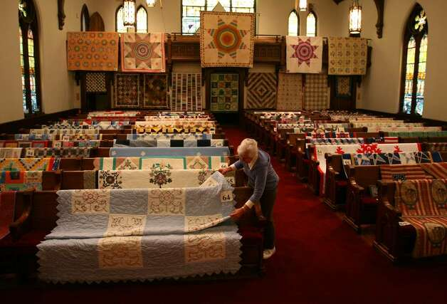 "Joanne Fabry of Fairfield arranges quilts on the pews of the Southport Congregational Church on Wednesday, March 3, 2010 in preparation for the annual quilt show at the church this Friday and Saturday. This year's show features 165 quilts as well as a special exhibit ""The World of Miniatures"". Photo: Brian A. Pounds / Connecticut Post"