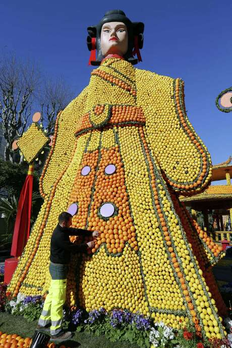 """A man works on a sculpture, made of oranges and lemons on February 12, 2015 in Menton on the French Riviera, ahead of the start of the """"Fete du Citron"""" (Lemon Festival). The theme of this 82nd edition, running from February 14 until March 4, 2015, is called 'the tribulations of a lemon in China'.  AFP PHOTO / VALERY HACHEVALERY HACHE/AFP/Getty Images Photo: VALERY HACHE, AFP / Getty Images / AFP"""