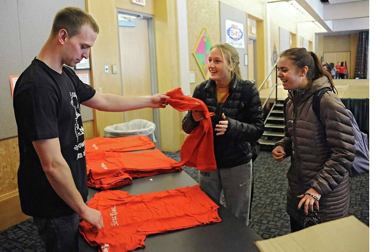 Senior Kyle Kennedy of Long Island hands out t-shirts to junior Sage Stebbins of Scituate, Mass, center, and sophomore Danielle DeGroot of Boonton, NJ before groups dance to the One Billion Rising anthem, ?