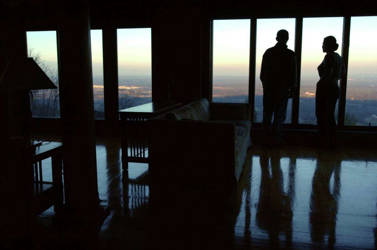 Kevin and Nicole Demarest take in the majestic eastern view from the living room of their town of New Scotland home on Tuesday November 23, 2004. Former Albany political figure Dan O'Connell used to live in the house, which sits on the Helderbergs. (Philip Kamrass/Times Union archive)