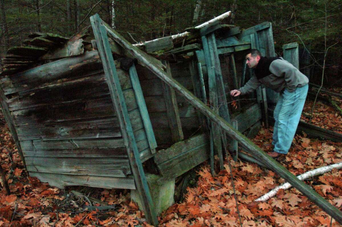 Kevin Demarest checks out dilapidated chicken coops on the property of his town of New Scotland home on Tuesday November 23, 2004. Former Albany political figure Dan O'Connell used to live in the house, and is alleged to have used the chickens for fighting. (Philip Kamrass/Times Union archive)