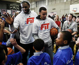 LeBron James (left) and the Warriors Stephen Curry talk to kids at a New York high school.