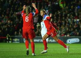 Alex Morgan (13) of the U.S. celebrates with Whitney Engen (6) after scoring their first goal during a women's friendly with England in Milton Keynes, England, on Friday.