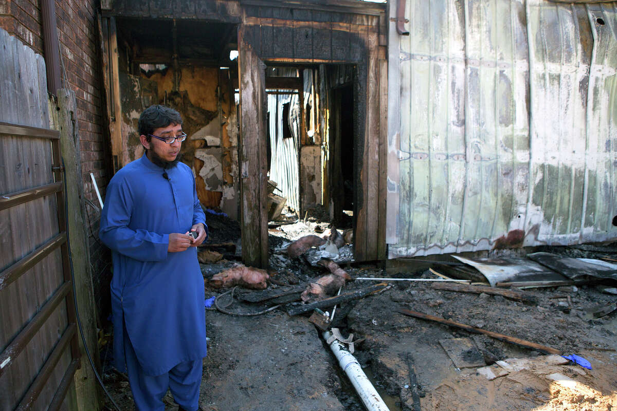 Ahsan Zahid, Assistant Imam, assistant priest in Islam, stands in front of the charred Quba Islam Institute after it burned Friday, Feb. 13, 2015, in Houston. The Houston Fire Department says nobody was hurt in the fire around 5:30 a.m. Friday at the Quba Islamic Institute. Authorities are trying to determine what caused the blaze in a rear part of the structure. (AP Photo/Houston Chronicle, Cody Duty) MANDATORY CREDIT