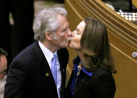 FILE - In this Jan. 12, 2015 file photo, Oregon Gov. John Kitzhaber kisses his fiancee, Cylvia Hayes, after he is sworn in for an unprecedented fourth term as governor in Salem, Ore. Kitzhaber announced his resignation Friday, Feb. 13, 2015, amid allegations Hayes used her relationship with him to enrich herself.  (AP Photo/Don Ryan, File)