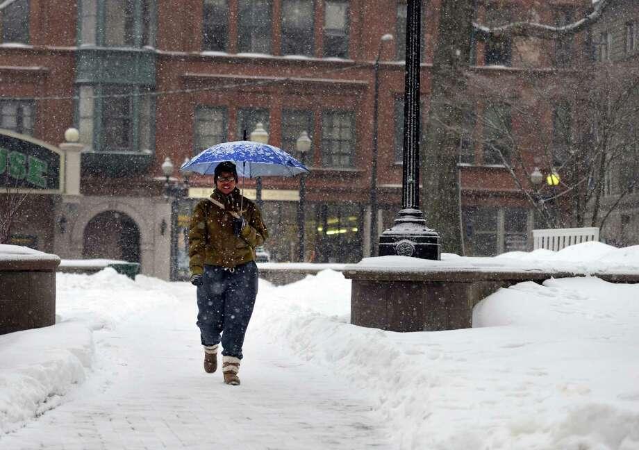 Kiesha Wilson, of Bridgeport, walks through a snowy McLevy Green Saturday, Feb. 14, 2015, as snow begins to blanket downtown Bridgeport. Photo: Autumn Driscoll / Connecticut Post