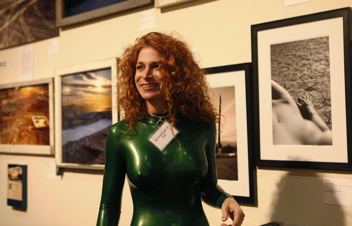 Model Schrodinger's Cat stands in front of a wall of erotic art photography during On the Edge 5: Erotic Art Exhibition at SOMArts in San Francisco on Friday, February 13.