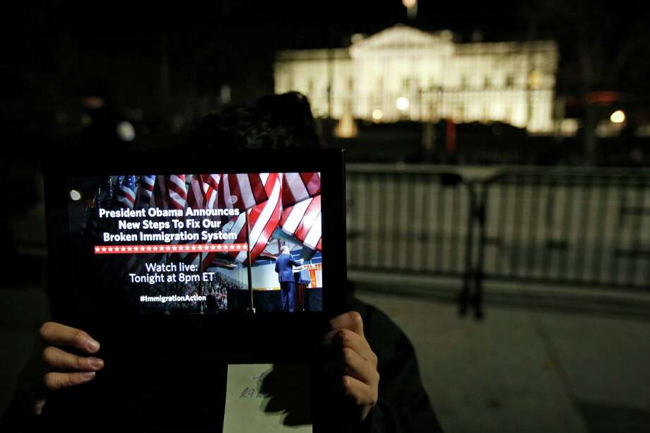 A supporter holds a tablet in front of the White House during a demonstration before the president announced executive actions on immigration during a nationally televised address in November. Photo: Alex Brandon /Associated Press / AP